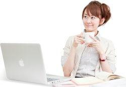 パソコンを机に乗せて笑っている可愛らしい女性の実写画像です。