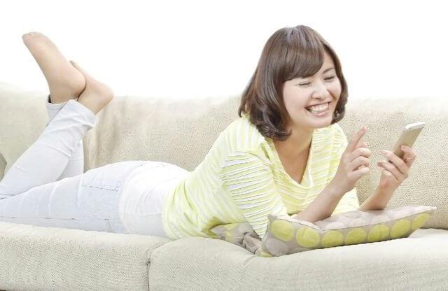 ソファーで嬉しそうにスマホを使う